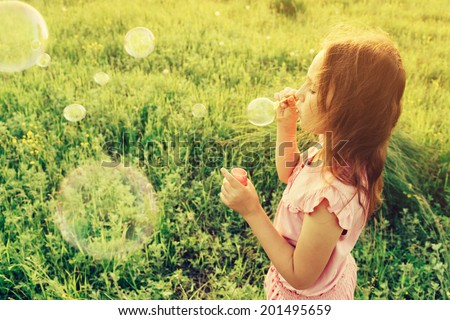 Little girl is blowing a soap bubbles in summer field. With instagram filter - stock photo
