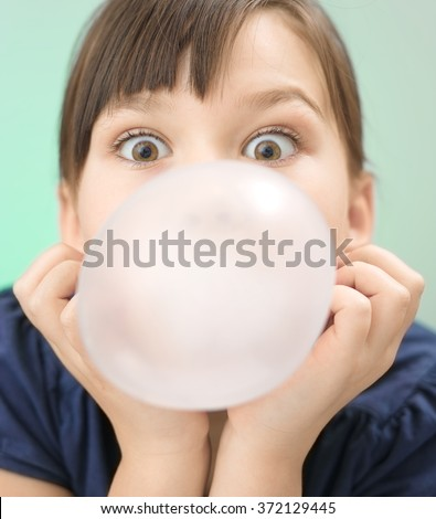 Little girl is blowing big bubble gum, closeup portrait - stock photo