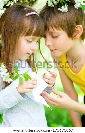 Little girl is blowing her nose, brother gives her nasal spray - stock photo