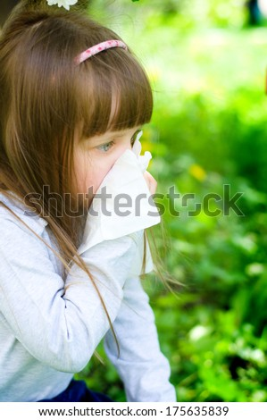 Little girl is blowing her nose while sitting on green grass - stock photo