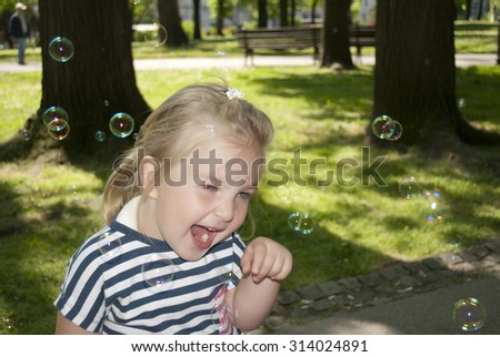 Little girl is chasing bubbles in the park - stock photo