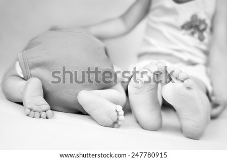 Little girl is comforting her baby brother. Black and white photo with soft focus on their feet. - stock photo