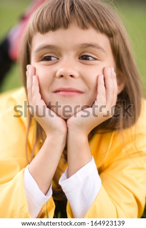 Little girl is daydreaming lying on green grass - stock photo
