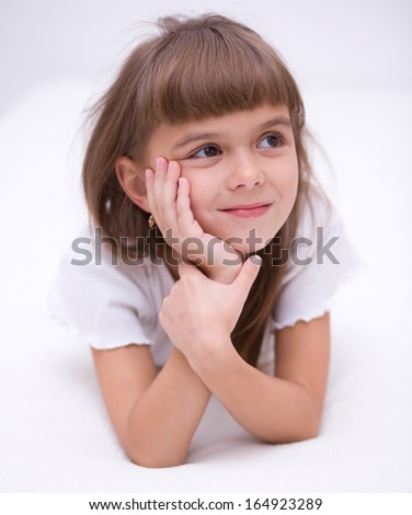Little girl is daydreaming lying on the floor - stock photo