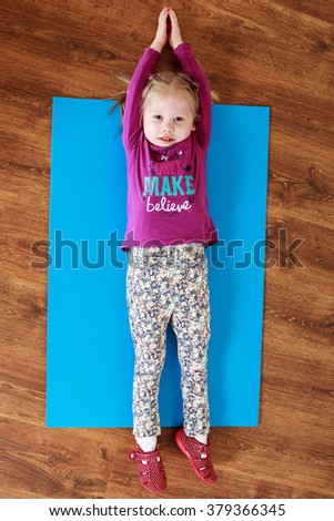 Little girl is doing stretching exercise  on a mat - stock photo