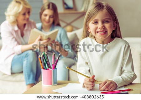 Little girl is drawing and smiling, in the background her mom and granny are reading a book while sitting on sofa at home - stock photo