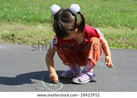 little girl is drawing on asphalt