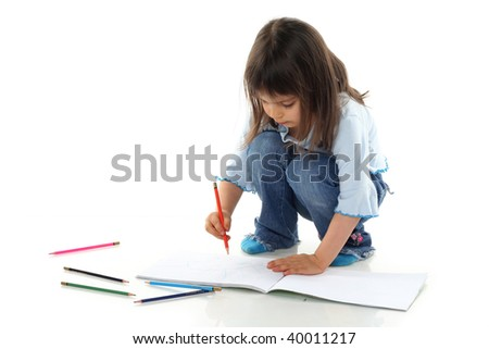 Little girl is drawing on white paper in album isolated
