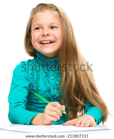 Little girl is drawing using color pencils while sitting at table, isolated over white - stock photo