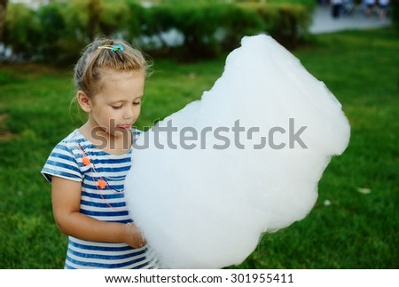 little girl is eating a cotton candy - stock photo