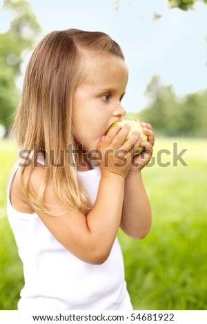 little girl is eating apple outdoor - stock photo