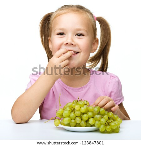 Little girl is eating grapes, isolated over white - stock photo