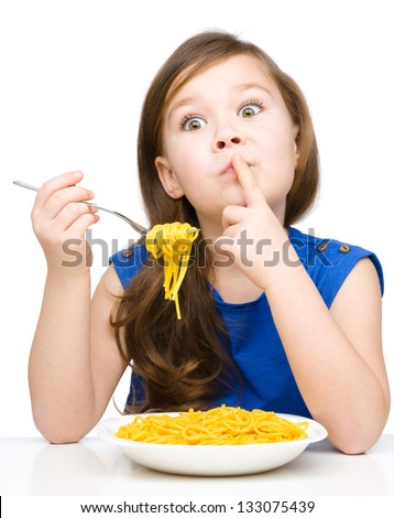 Little girl is eating spaghetti while showing hush gesture, isolated over white - stock photo