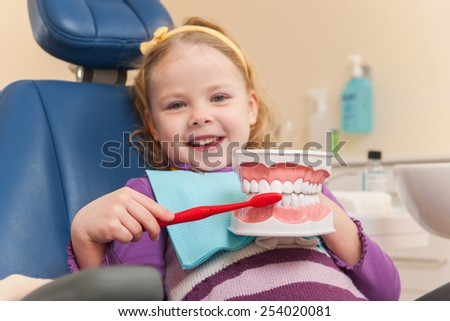 Little girl is having her teeth examined by dentist. girl holding artificial teeth and brush and smiling - stock photo