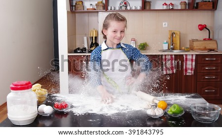 little girl is helping to bake  in a messy  kitchen - stock photo