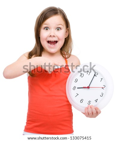 Little girl is holding big clock and pointing at it, isolated over white - stock photo