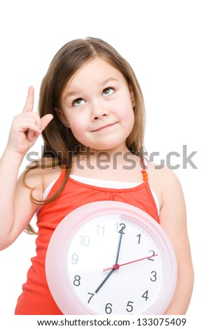 Little girl is holding big clock and pointing up, isolated over white - stock photo