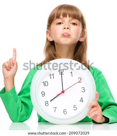 Little girl is holding big clock while pointing up with her index finger, isolated over white - stock photo