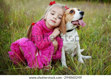 little girl is holding dog outdoors - stock photo