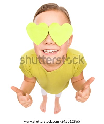 Little girl is holding hearts over her eyes and showing thumb up sign, fisheye portrait, valentine concept, isolated on white - stock photo