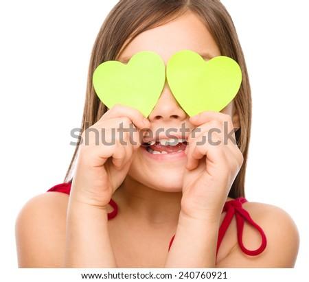 Little girl is holding hearts over her eyes, valentine concept, isolated on white - stock photo
