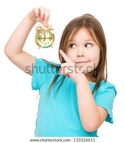 Little girl is holding small alarm clock and pointing at it, isolated over white - stock photo