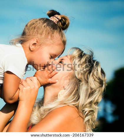 little girl is kissing her mother - stock photo