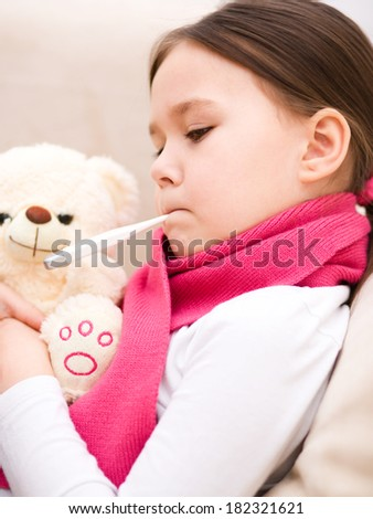 Little girl is laying on sofa with thermometer in her mouth - stock photo