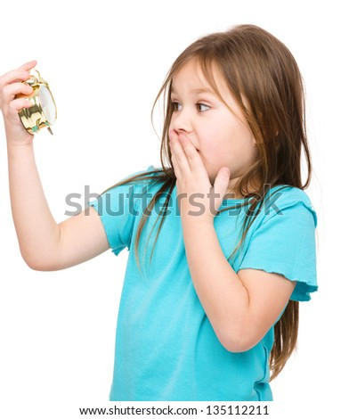 Little girl is looking at alarm clock while covering her mouth in panic, isolated over white - stock photo