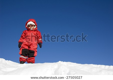 little girl is looking down from a hill on a sunny winter day