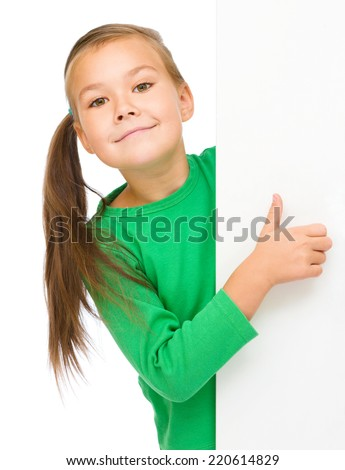 Little girl is looking from out blank board and showing thumb up sign, isolated over white - stock photo
