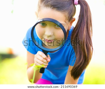 Little girl is looking through magnifier, outdoor shoot - stock photo