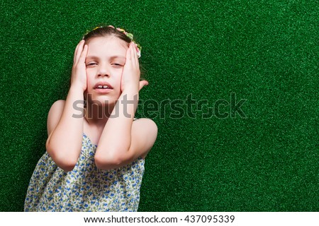 Little girl is lying on artificial grass. She is having headache. - stock photo