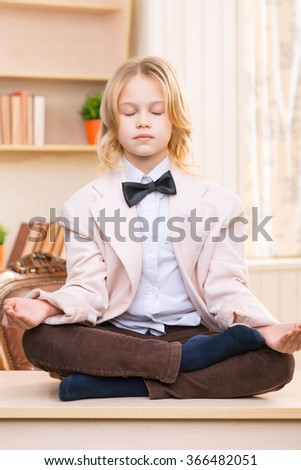 Little girl is meditating on the desk.
