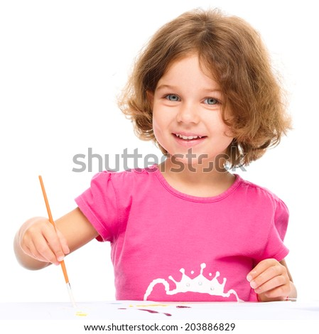 Little girl is painting with gouache while sitting at table, isolated over white - stock photo