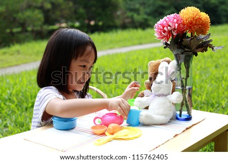 Little girl is playing her toys on a garden table together with a cuddly bear and a rabbit. - stock photo