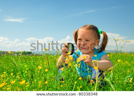 Little girl is playing on green meadow and examining field flowers using magnifying glass