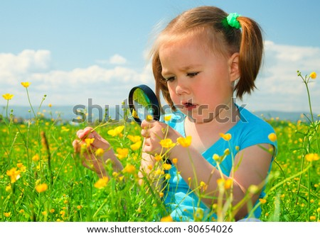 Little girl is playing on green meadow and examining field flowers using magnifying glass - stock photo