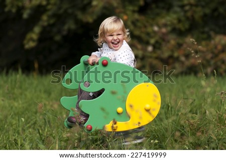 Little girl is playing on playground - stock photo