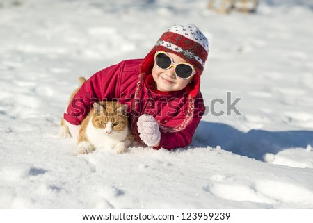 Little girl is playing outside in cold winter. - stock photo