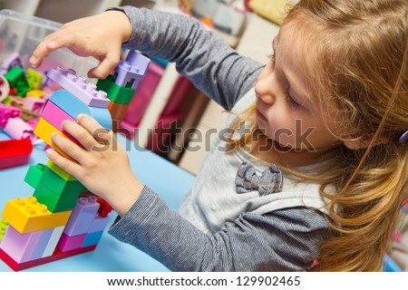 Little girl is playing with building bricks - stock photo
