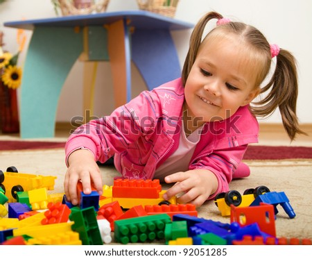 Little girl is playing with building bricks in preschool while laying on floor - stock photo