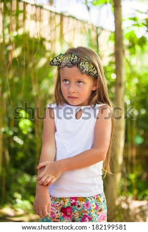 Little girl is playing with butterfly in butterflies garden