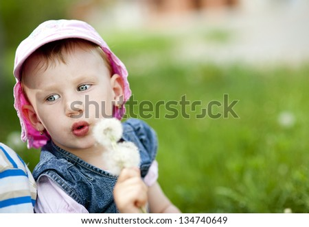 Little girl is playing with dandelion
