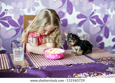 Little girl is playing with her little puppy - stock photo