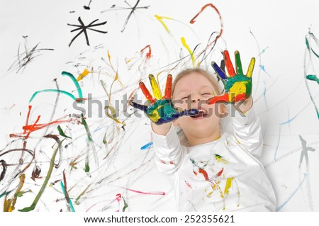 Little girl is playing with paints. She is painted all over and is lying on painted floor. - stock photo