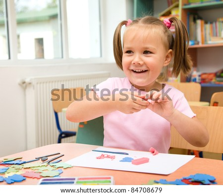 Little girl is playing with plasticine in preschool - stock photo