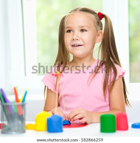 Little girl is playing with plasticine while sitting at table - stock photo