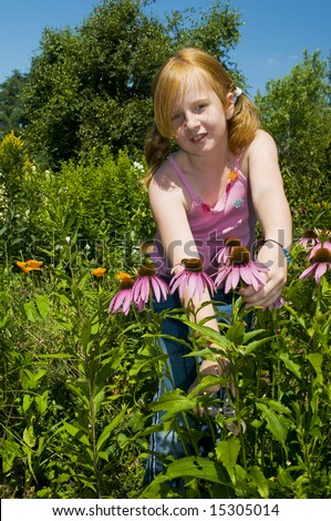 Little girl is plucking flowers in the garden - stock photo