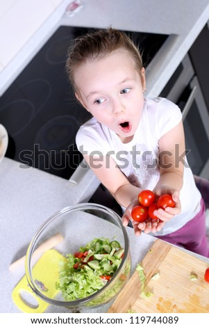 little girl is preparing salad at the table - stock photo
